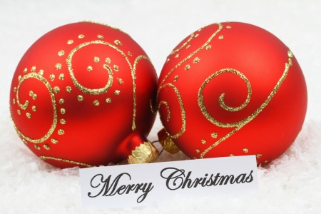Merry Christmas card with red baubles on snowy surface