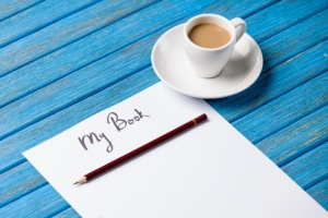 pencil and paper with inscription r cup of coffee on blue wooden table